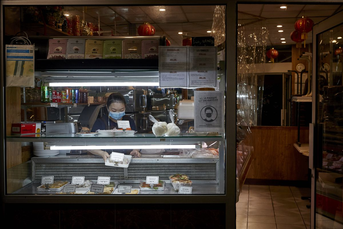 A woman in a mask leans over a deli case at night.