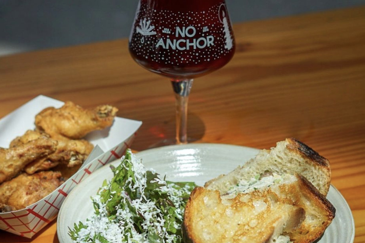"""A glass of beer that says """"No Anchor"""" next to a paper tray filled with wings and a sandwich on a plate with a side salad"""