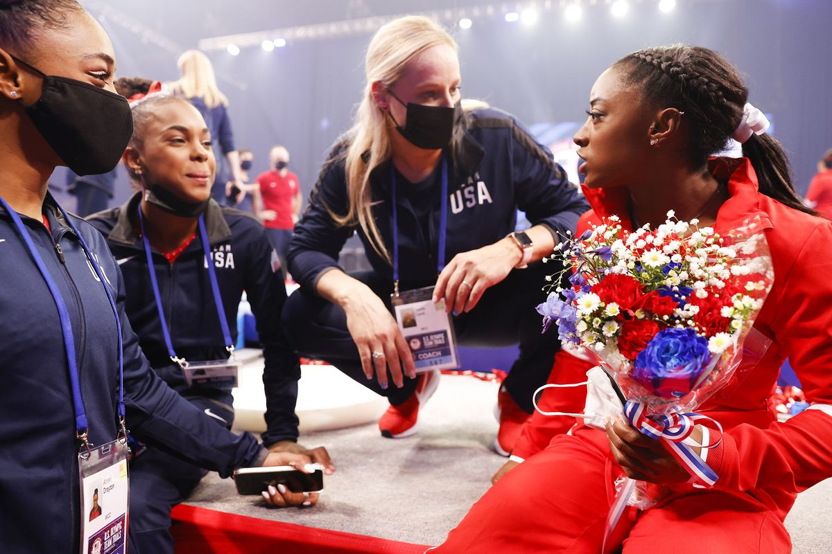 Simone Biles with a bouquet of flowers talking to her coaches.