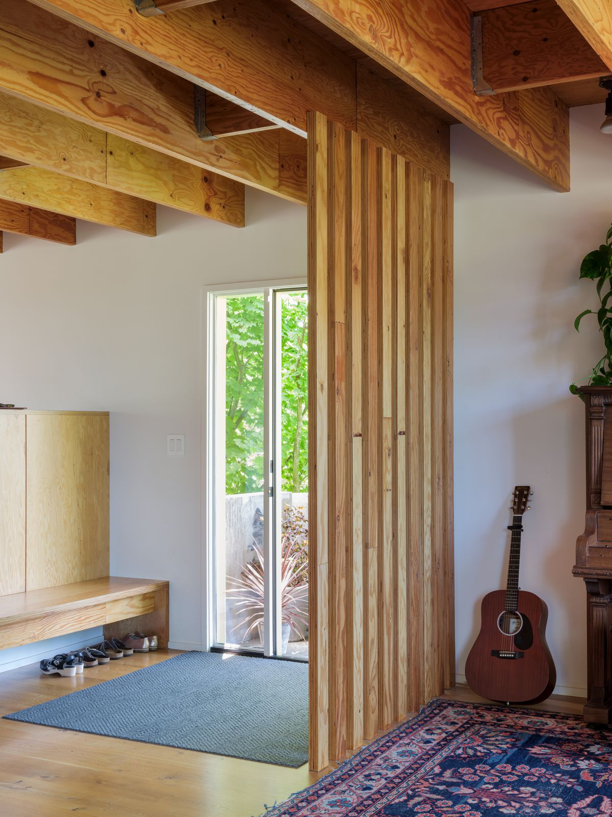 A living area with a patterned area rug, wooden room divider, and bench. There is a guitar leaning against the wall. There are shoes under the bench. There are glass doors.