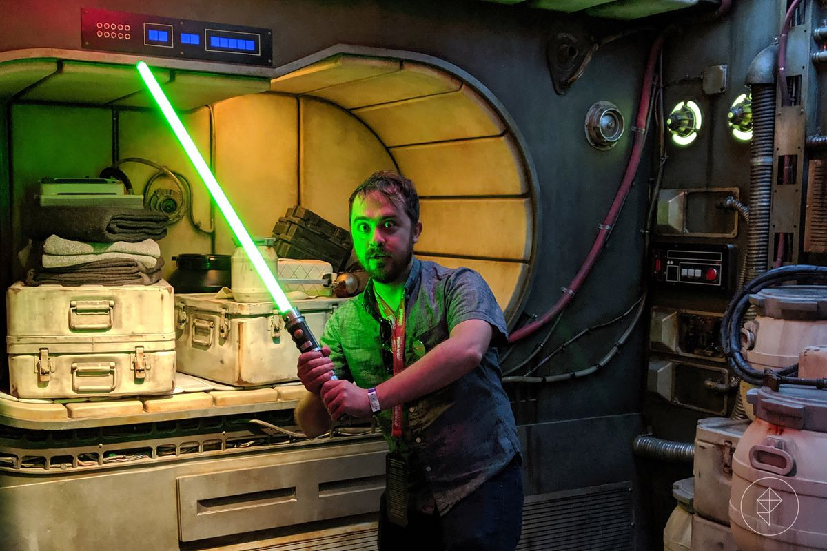 Chris Plante vamps with his new lightsaber inside the lounge of the Millennium Falcon during a special press preview of Star Wars: Galaxy's Edge in Anaheim, California in 2019.