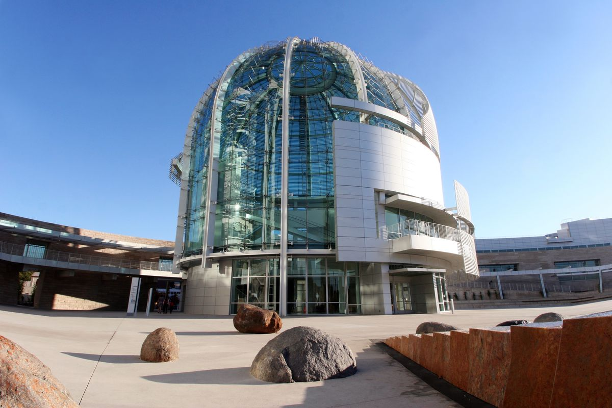 The exterior of the San Jose City Hall. There is a rotunda in the center which is glass. In the foreground is a courtyard with large rocks.