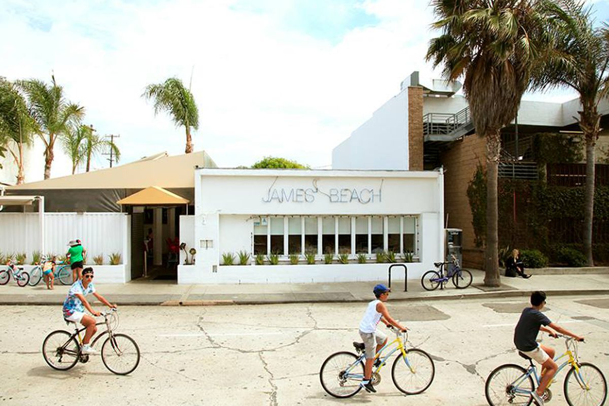 Three bike riders pass in front of a white restaurant building.