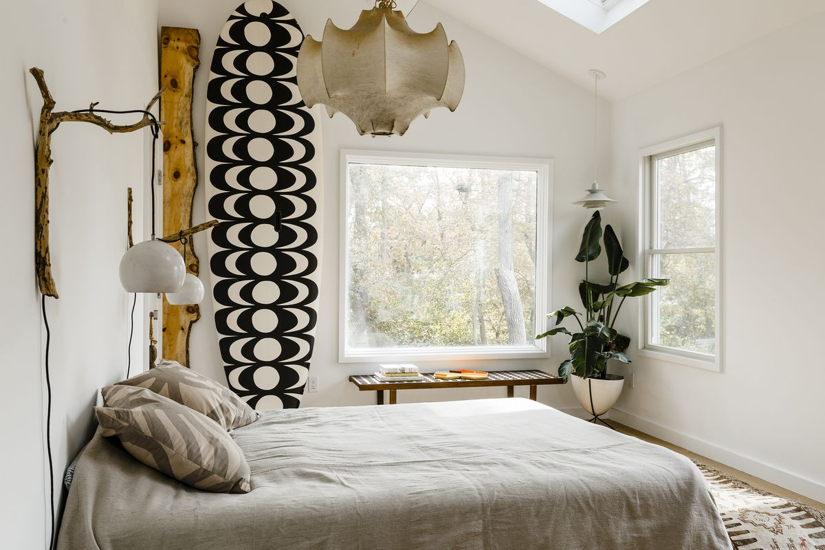 A bedroom with white walls and large windows features an organic color scheme with beige bedding, a graphic black and white surf board in the background, and tree branches as decor.
