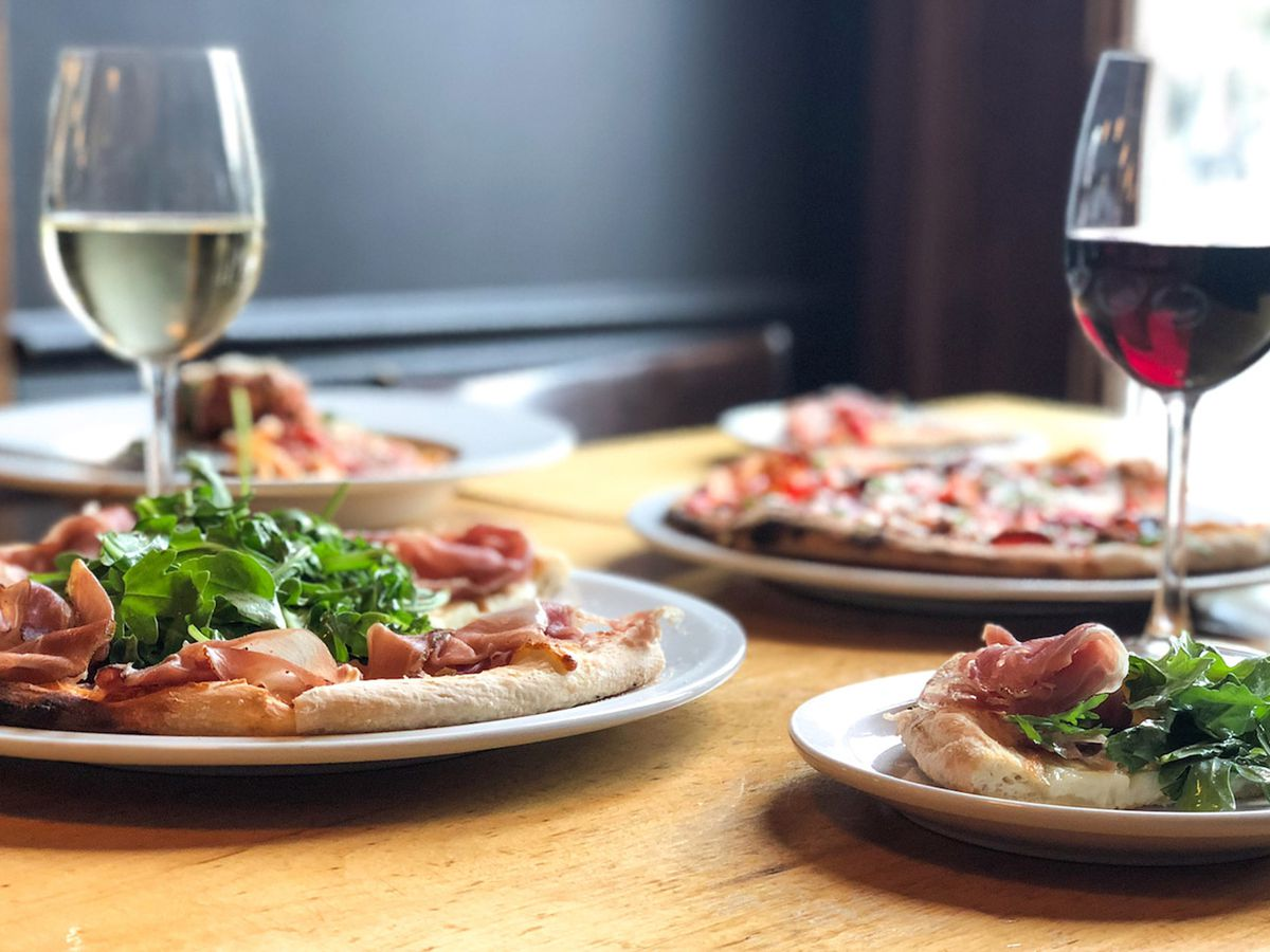 Glasses of wine and pizzas on a table.