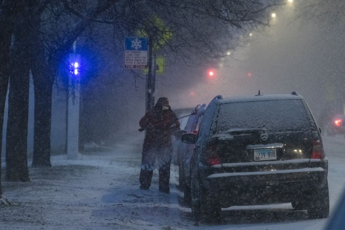 A woman uses a brush to brush snow off her vehicle near University of Chicago, as a snow storm batters Chicago, Tuesday, Dec. 29, 2020.