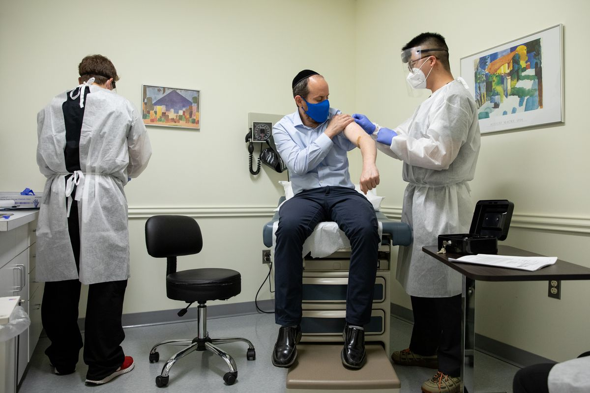 A man sits on an exam table while his arm is swabbed and another man looks on. All three are wearing masks.