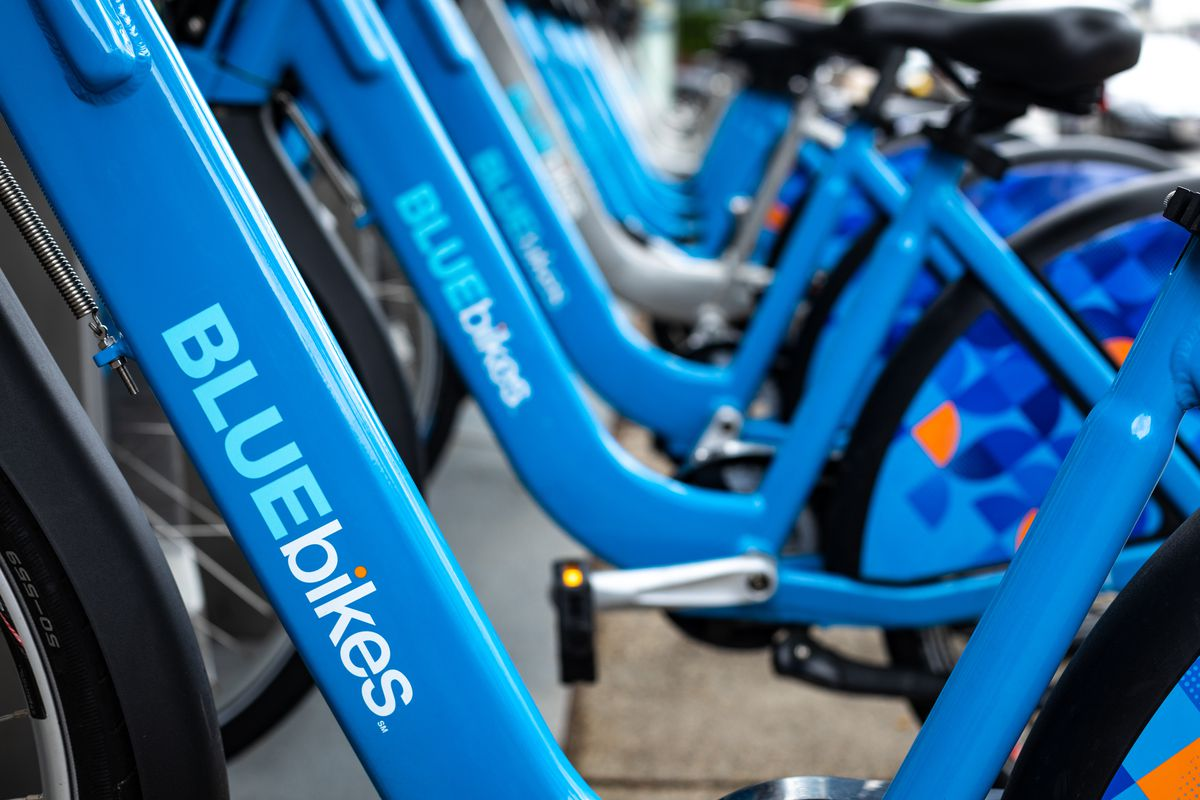 A bike-share kiosk with several bikes in a row attached.