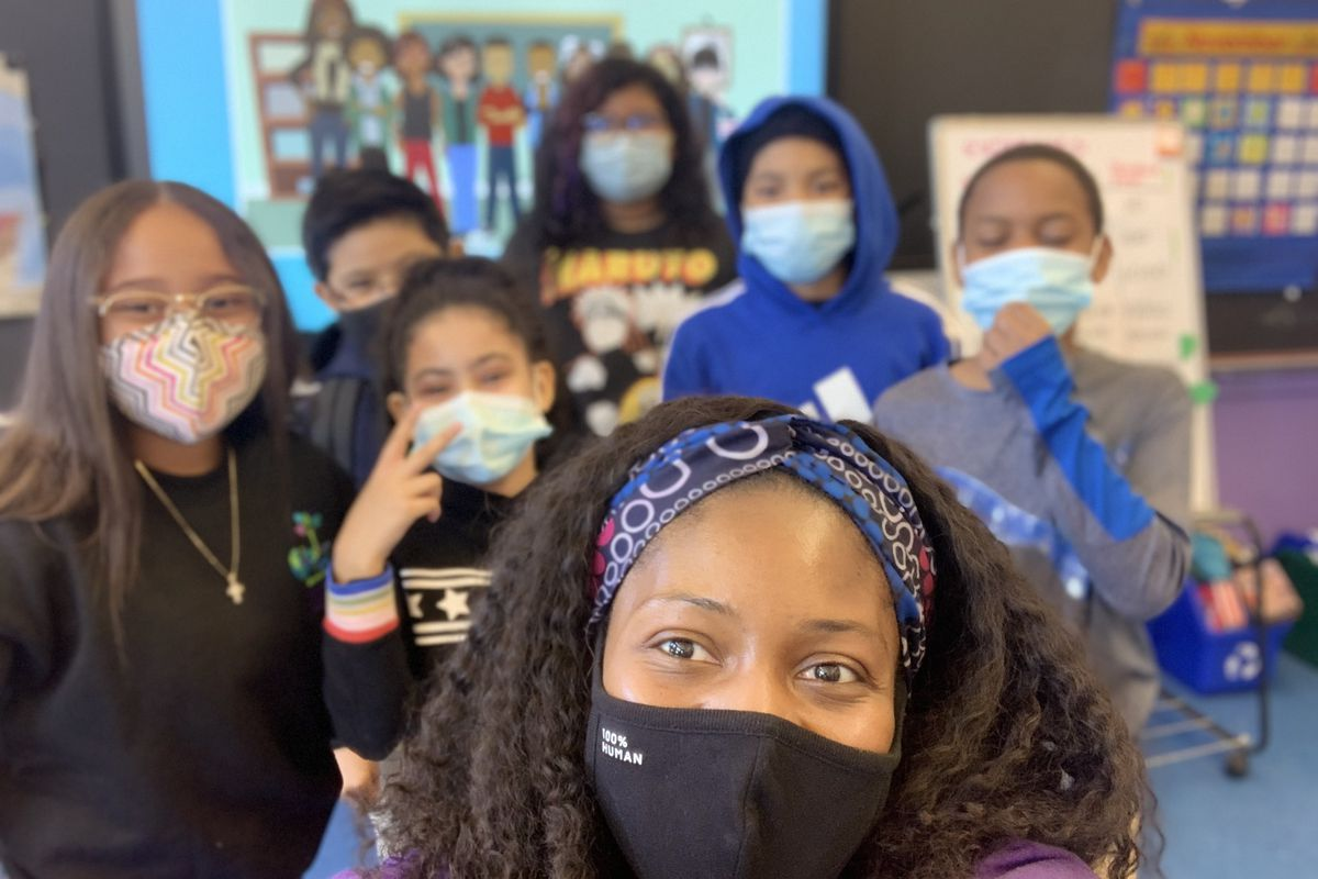 A woman in a mask is pictured with six masked students.
