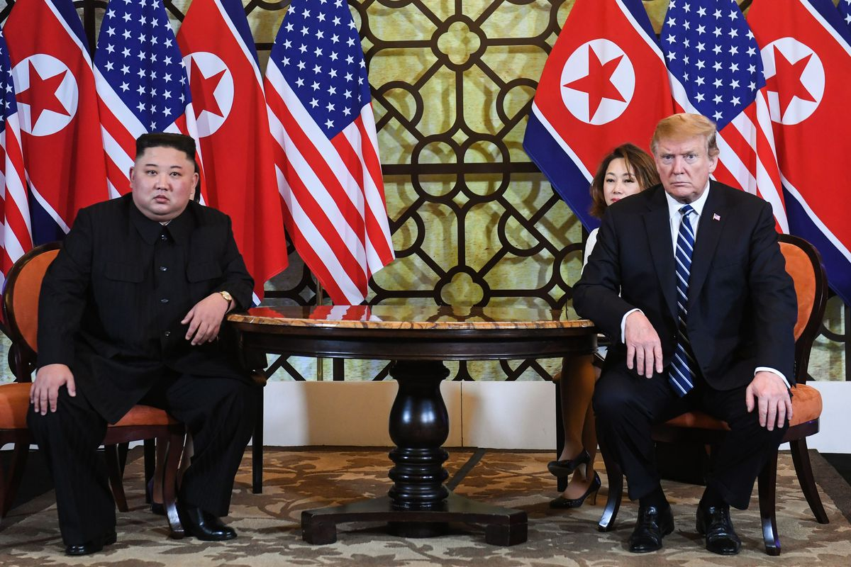 Trump and Kim at a table in front of press.