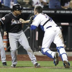 Miami Marlins' Donovan Solano, second from left, is tagged out during a rundown by New York Mets catcher Josh Thole during the sixth inning of a baseball game on Friday, Sept. 21, 2012, in New York.