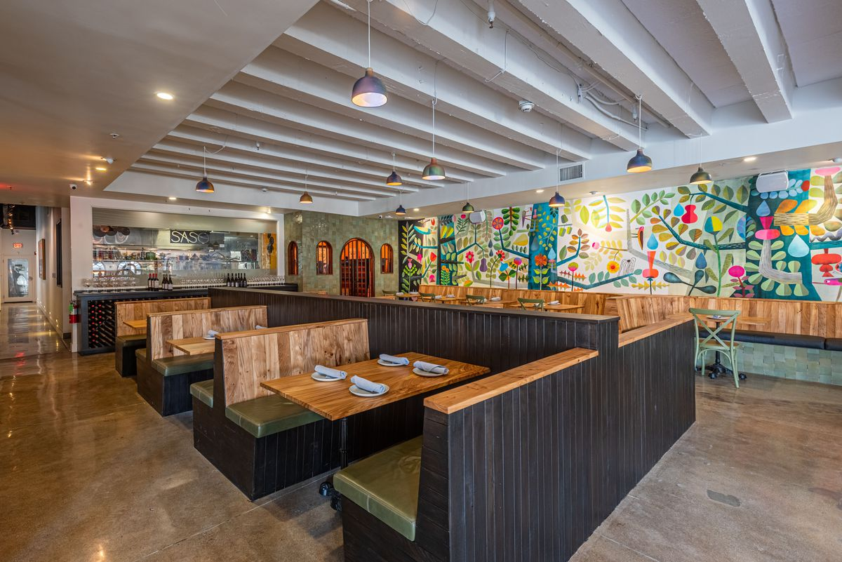 Wooden booths and a colorful back wall with a new restaurant.