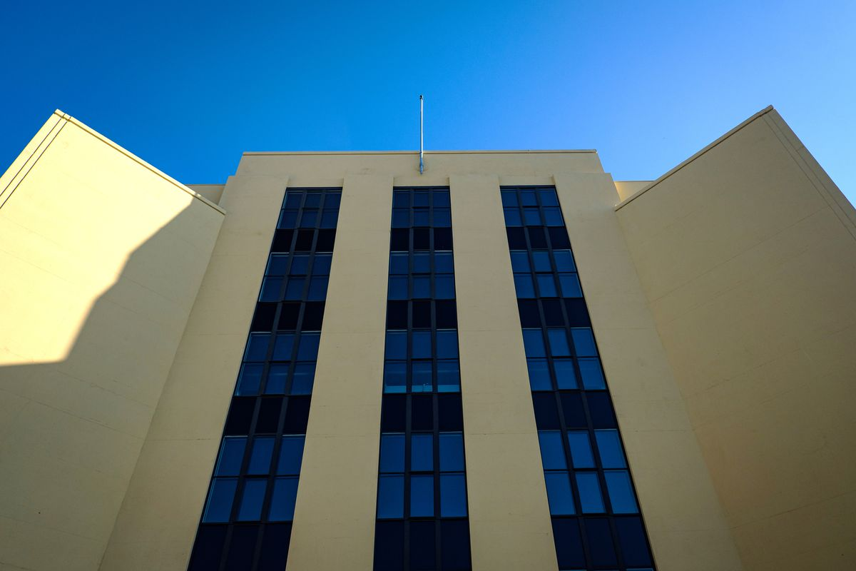 """A photo looking up the front facade of a yellow, mid-rise building. Two """"wings"""" of the building come out like arms readying for an embrace. Three parallel ribbons of windows run up the central section of the facade."""