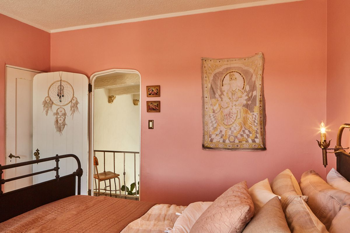 Pinks walls in a bedroom. Iron bed has a blush colored quilt, with lots of neutral and pink colored pillows on the bed. A white door is open with a dream catcher on it. A scarf hangs on the wall.