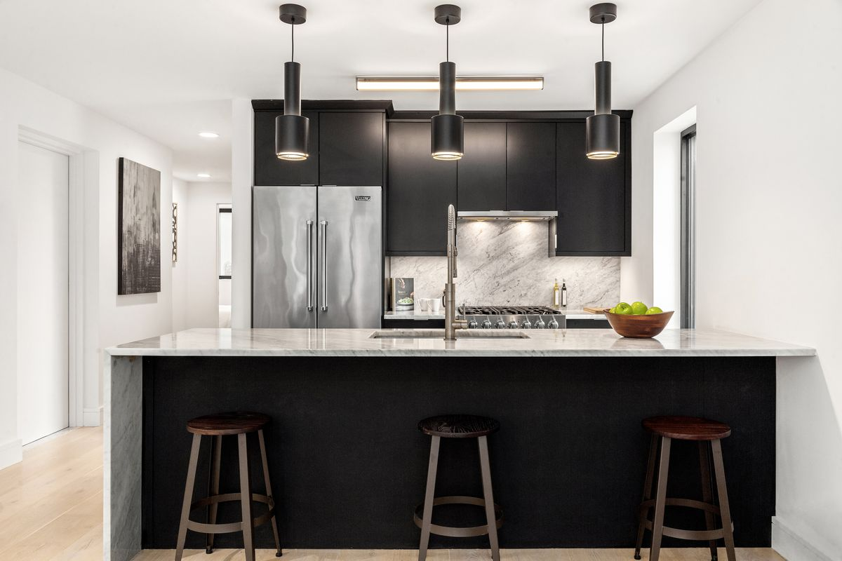 A kitchen with dark wood cabinetry, a large kitchen island, and three chairs.