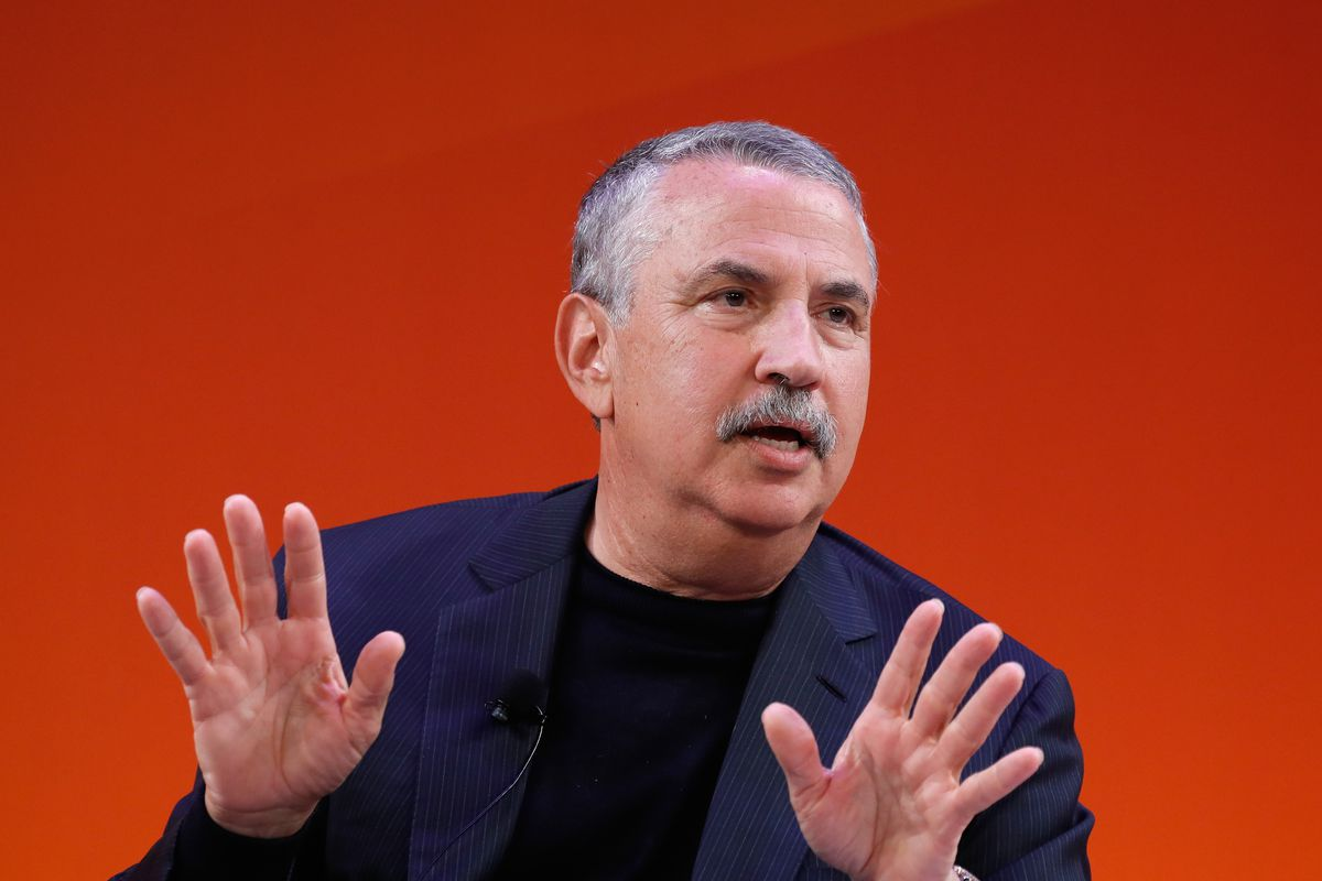 A man with salt-and-pepper hair and a bushy mustache addresses an audience from onstage, on a warm red background.