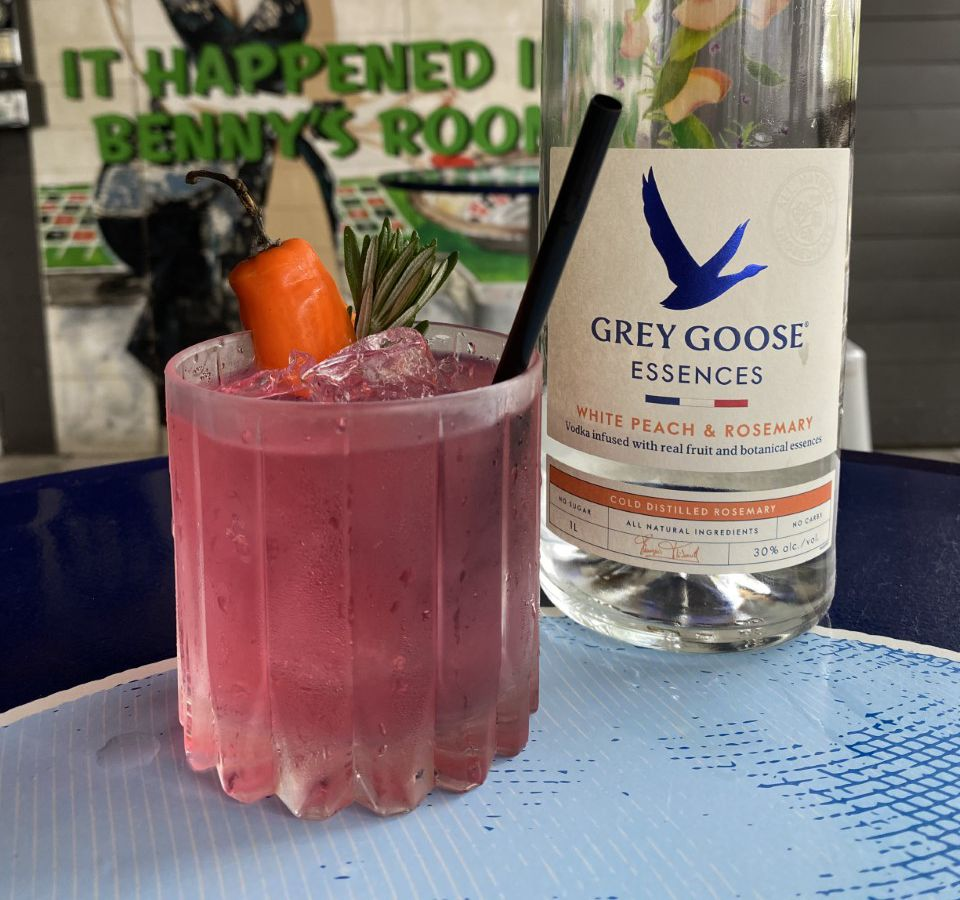 A pink cocktail in a short glass is topped with a carrot and a rosemary sprig.