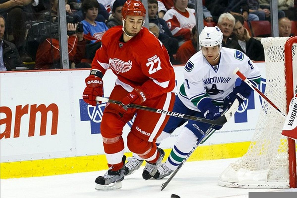 Feb. 23, 2012; Detroit, MI, USA; Detroit Red Wings defenseman Kyle Quincey (27) and Vancouver Canucks center Cody Hodgson (9) battle for the puck in the second period at Joe Louis Arena. Mandatory Credit: Rick Osentoski-US PRESSWIRE