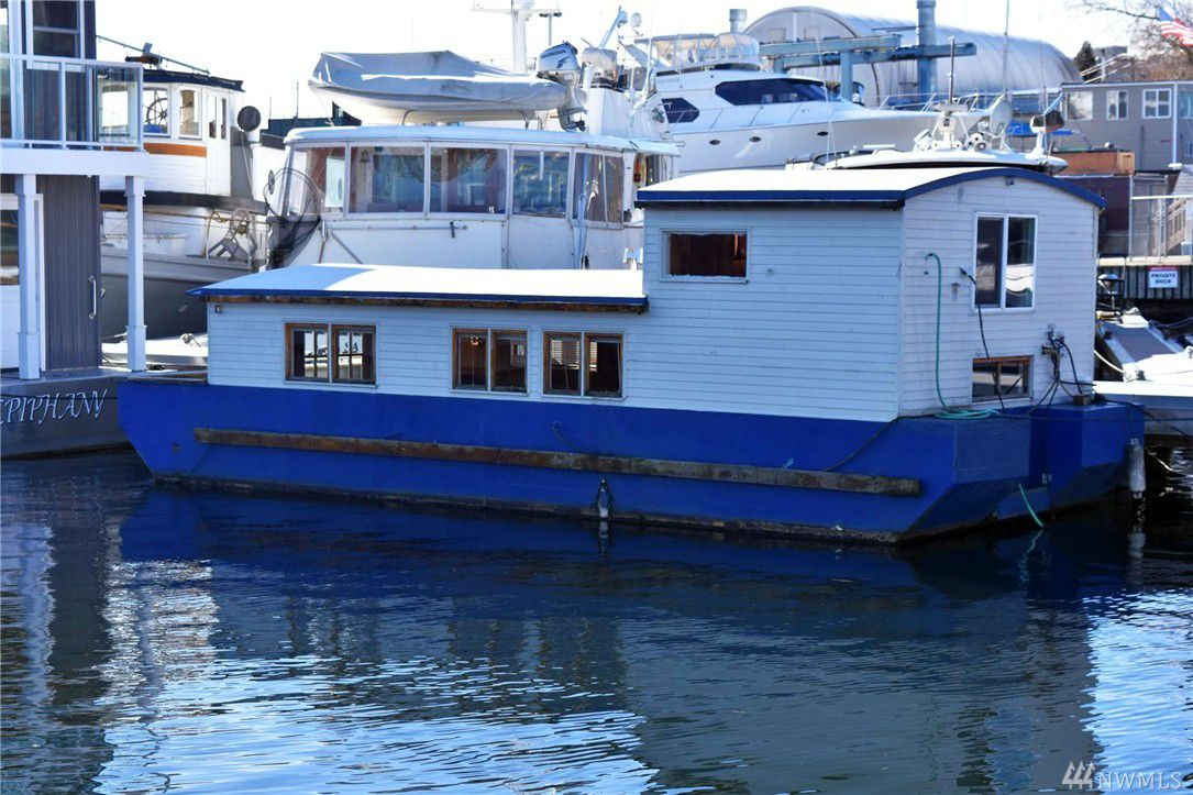 Emma the Houseboat, viewed from the side. Blue base with a white top. Can see the shape of top loft.