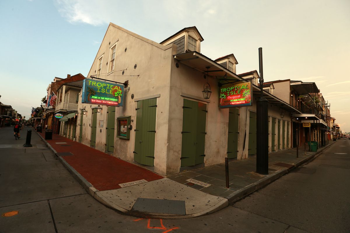 A corner bar in New Orleans's French Quarter is pictured closed and boarded up with green shutters