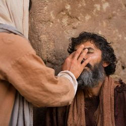 Jesus Christ heals the blind man by putting clay on his eyes in this image from a Bible Video depicting the events in John 9.