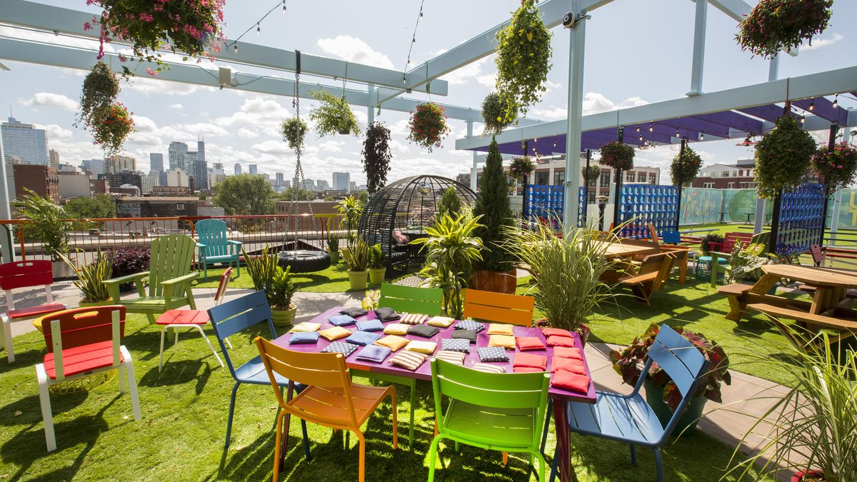 A rooftop bar with colorful seats, hanging planters, and a view of Chicago's skyline.