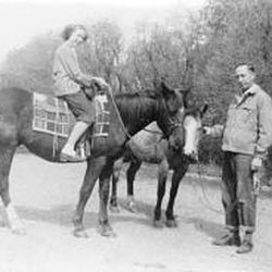 A young Carolyn Tanner sits on her horse near her father before leaving home.