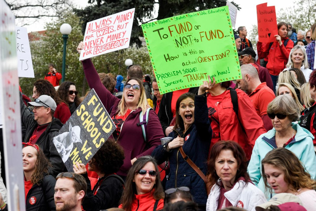 Educators wearing red and holding signs rally for more education funding at the Colorado Capitol on April 26, 2018.