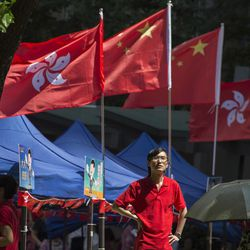 A man stands near Chinese and Hong Kong flags at an event to show support for the Chinese president's visit at a gathering in Hong Kong, Thursday, June 29, 2017. Hong Kong is planning a big party as it marks 20 years under Chinese rule. Fireworks, a gala variety show and Chinese military displays are among the official events planned to coincide with a visit by Xi starting Thursday for the occasion.