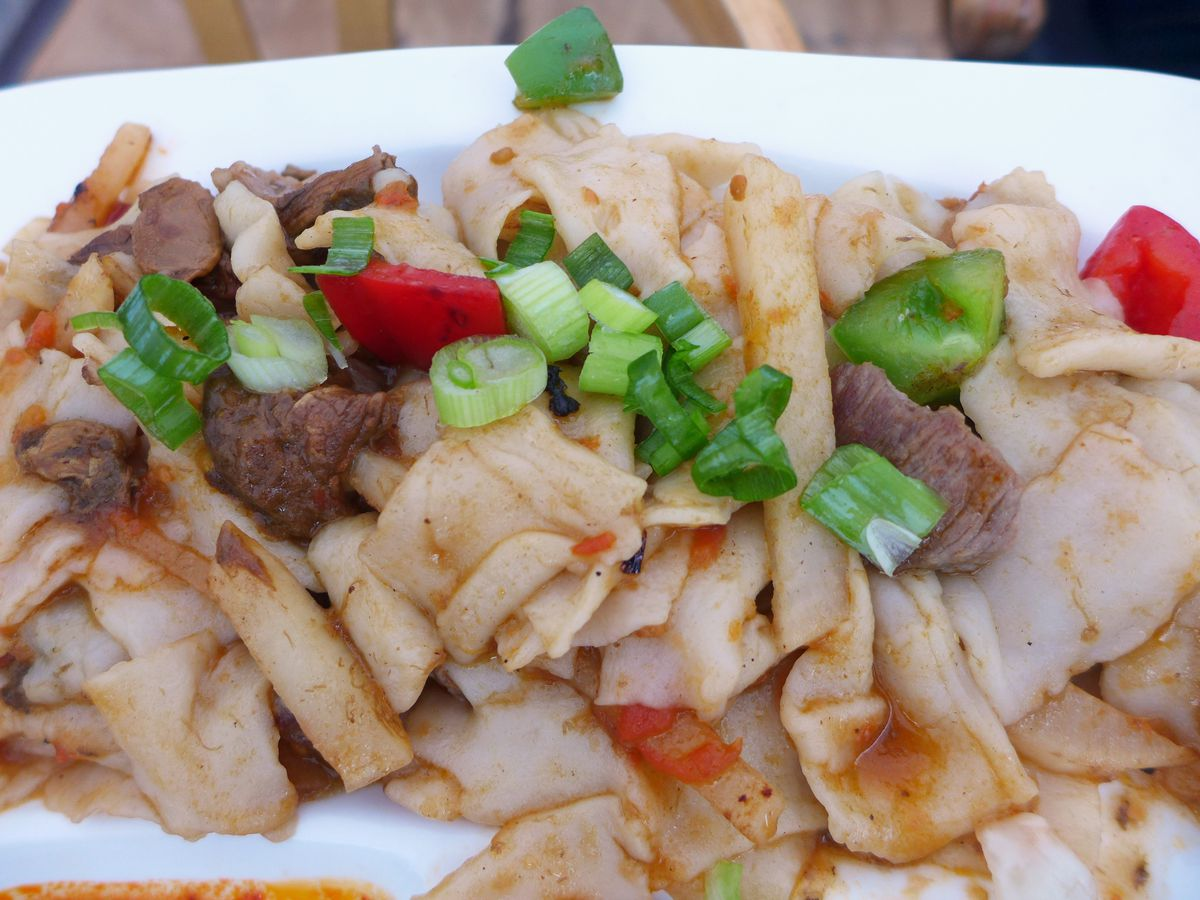 Irregular swatches of wheat noodle dotted with lamb and red bell peppers.