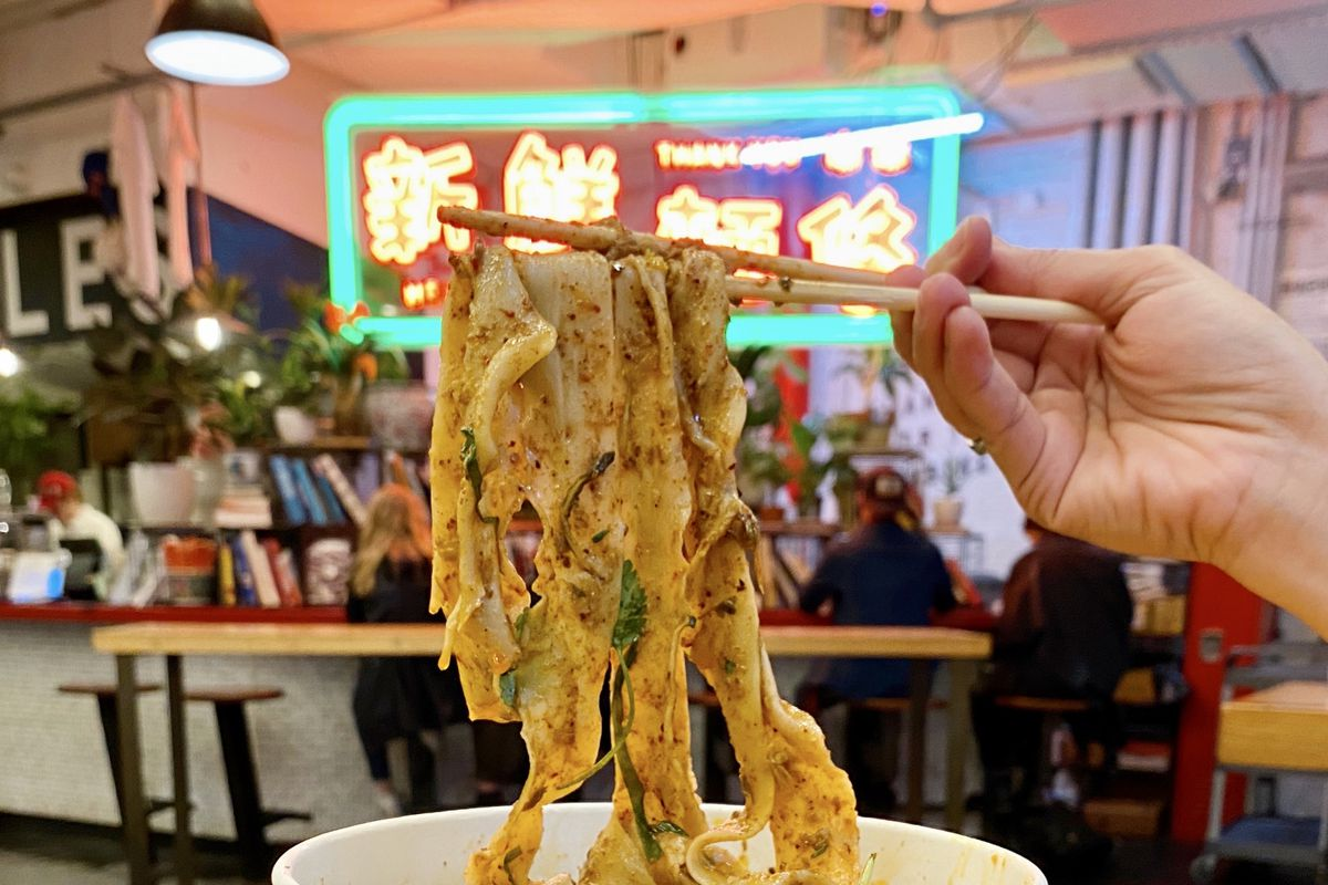 A person holds up hand-pulled noodles with a pair of chopsticks at Very Fresh Noodles's stall inside Chelsea Market