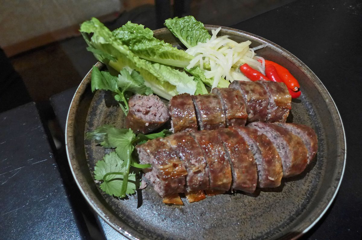 A dark thick sausage sliced and sided with chiles and raw ginger.
