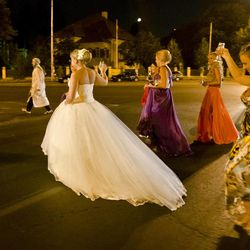 In this Sunday, Aug. 26, 2012 photo shot under iodine street lighting, a Romanian bride and wedding guests cross the road through traffic at the Triumph Arch in Bucharest, Romania. The arch, a replica of the Arc de Triomphe in Paris, the French capital, is a rendezvous place for brides on the wedding night for the bride stealing ritual. The ancient Romanian tradition of bride stealing is getting bigger, brasher and an increasingly common sight in the Romanian capital, the region's undisputed party town.