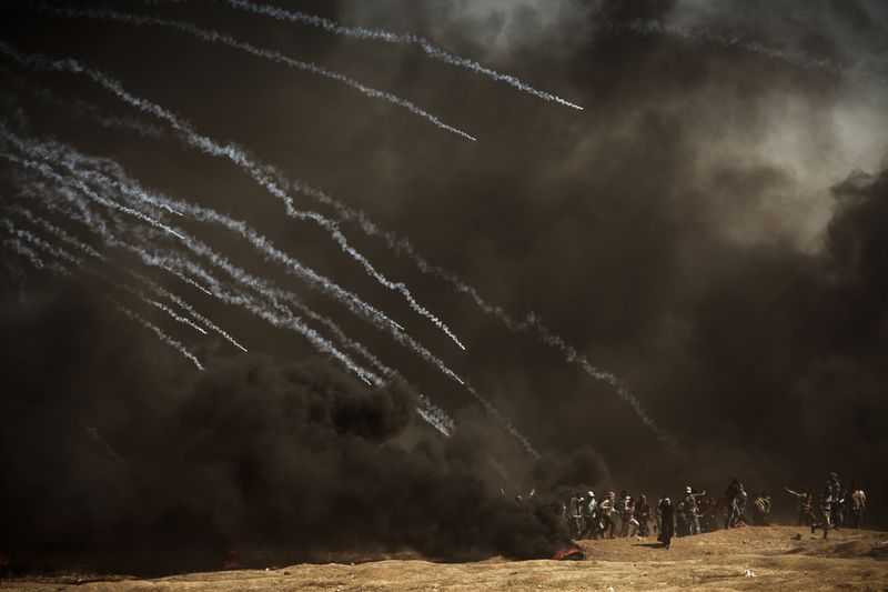 Tear gas canisters rain on a group of demonstrators at the border fence with Israel as mass demonstrations continue on May 14, 2018 in Gaza City, Gaza.
