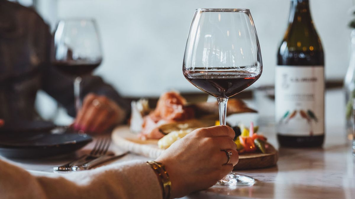 A hand holds a glass of red wine in front of a platter of charcuterie, with a bottle of red wine in the distance. The two guests, out of frame, are sitting at the bar at Normandie in Southeast Portland.
