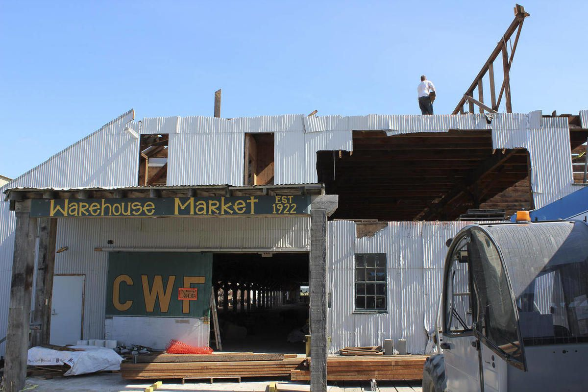 """In this Aug. 11, 2012, photo, workers """"deconstruct"""" a building that once was a warehouse for Columbia Wards Fisheries in Kenai, Alaska. Construction materials from the building will be used in other local facilities."""