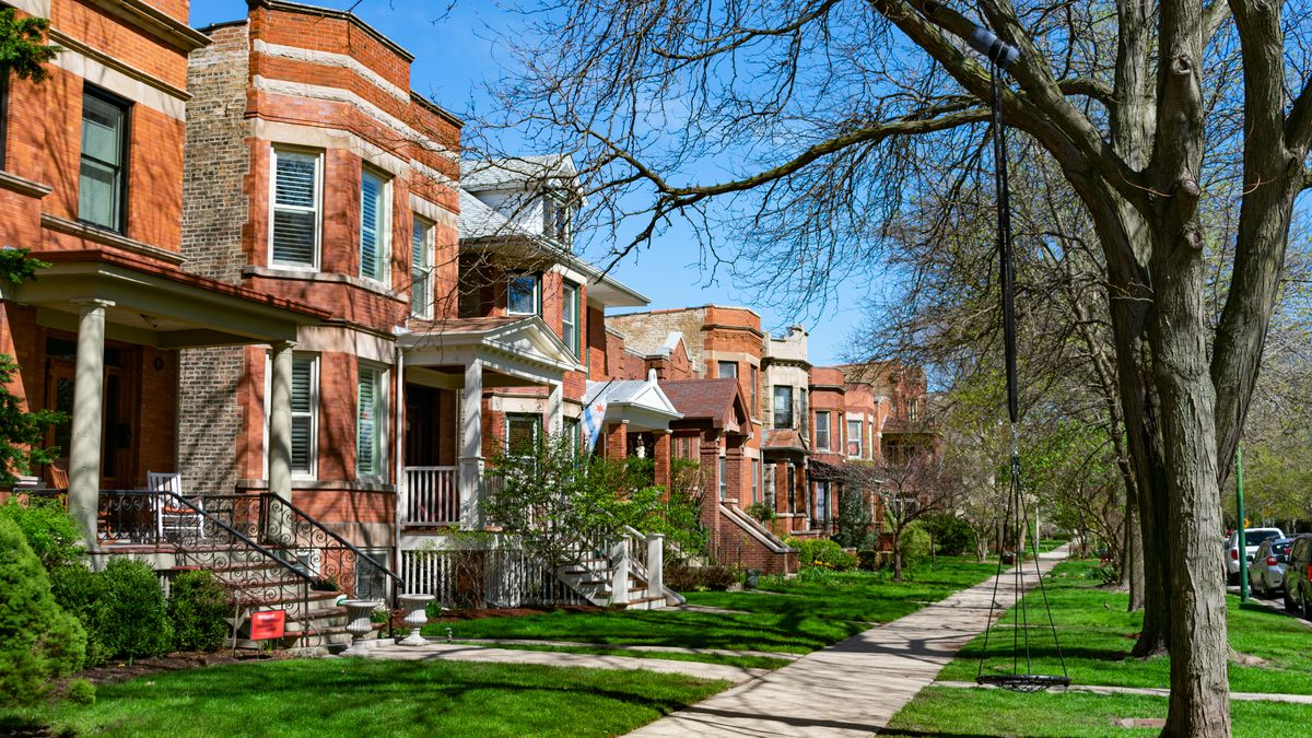 A row of handsome brick houses and apartments are seen along a sidewalk with green grass and trees just showing the first signs of spring.