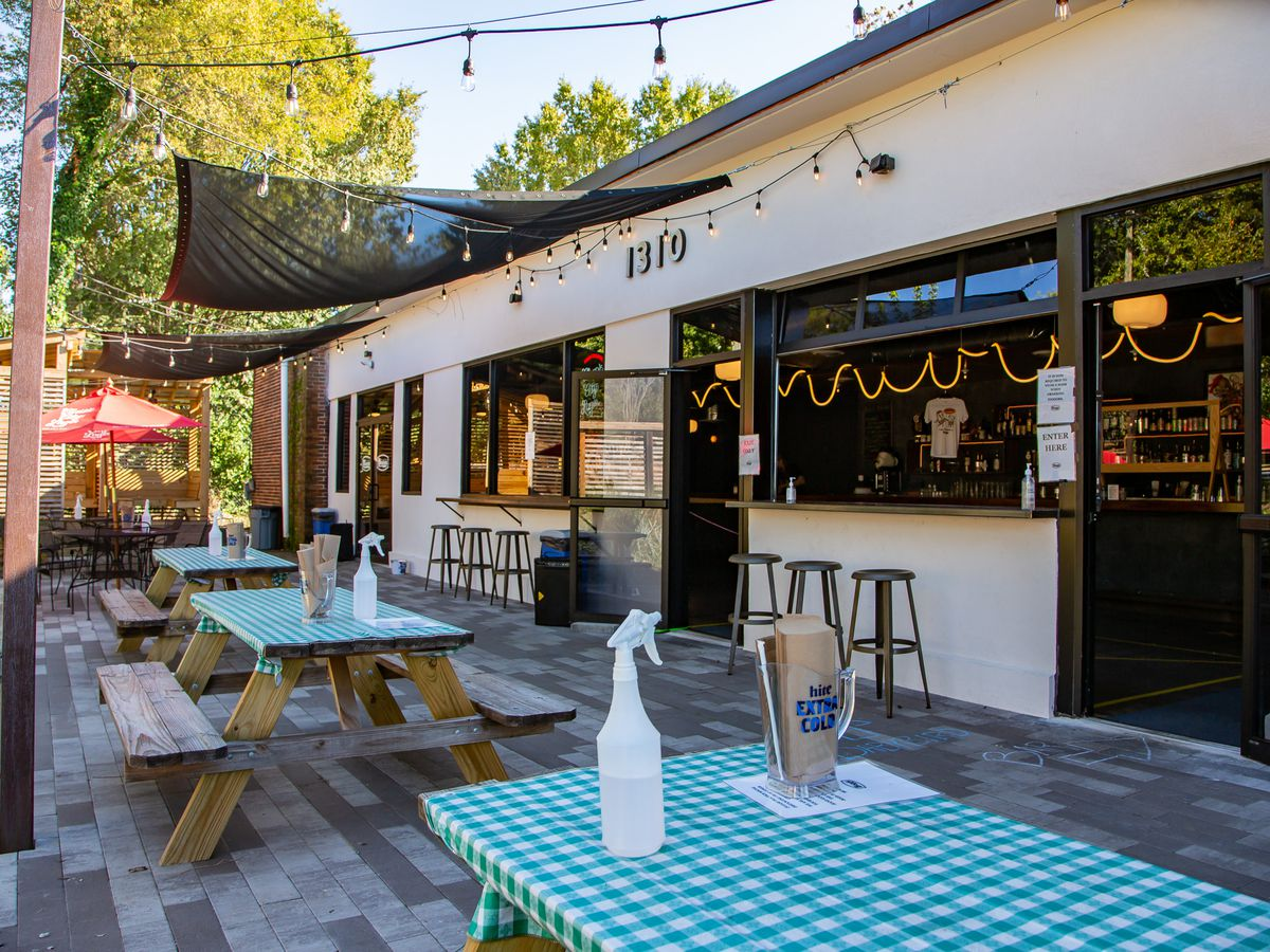The patio at Boggs Social and Supply in West End Atlanta with three picnic tables covered in green checked plastic table cloths, spray bottles filled with sanitizing spray. String lights are hung above and the windows to the to-go bar are open
