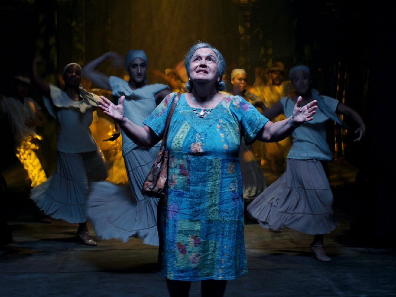Actor Olga Merediz in a blue floral house dress raises her hands under a spotlight while latinx dancers dressed in all white frame her in the background.