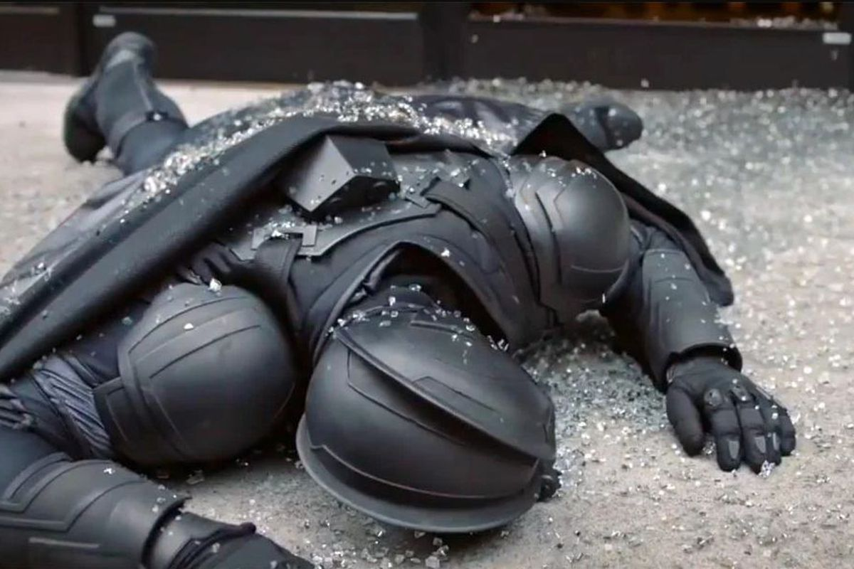 An unnamed bank robber dressed in a costume reminiscent of Batman in the Nolan movies likes prone on the floor, in the third episode of HBO's Watchmen.