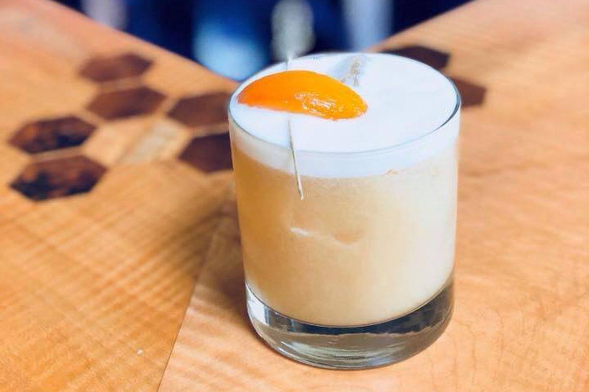 Pale orange cocktail with peach garnish on a wooden bar with honeycomb engraving.