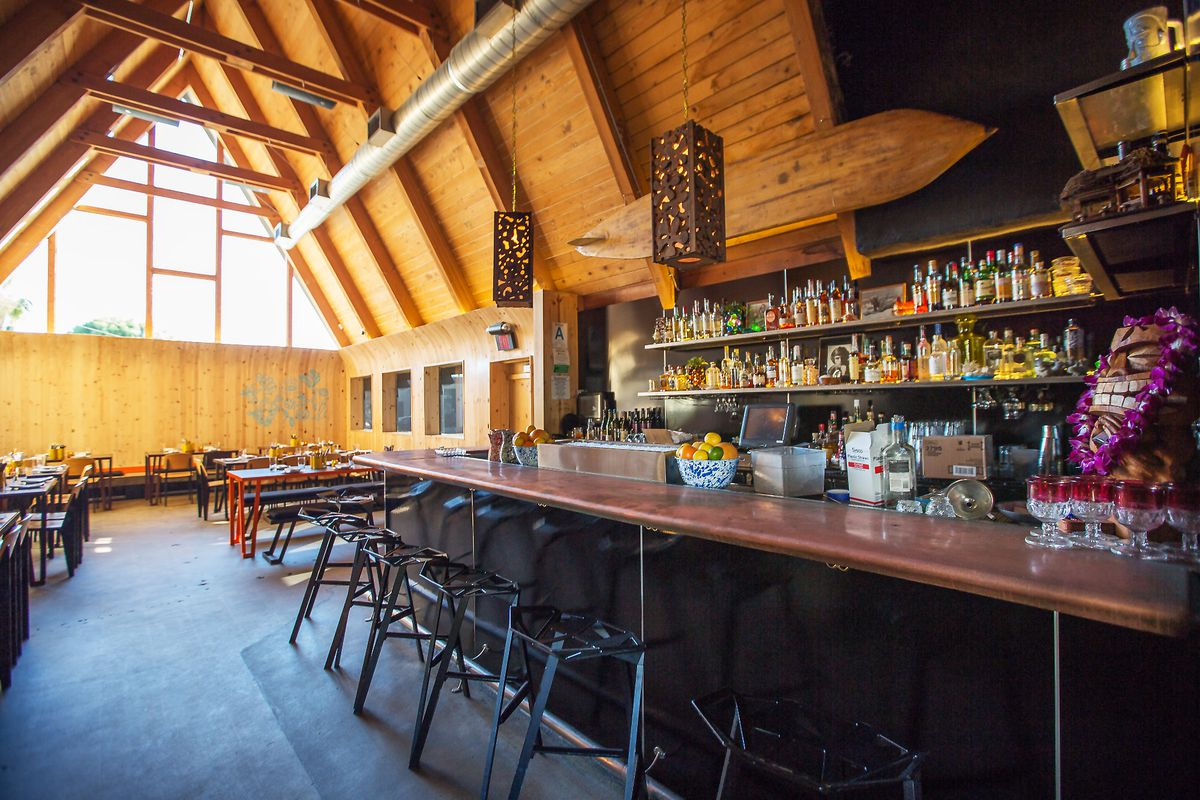 An a-frame style restaurant lets in light from a far window, with a bar up close.