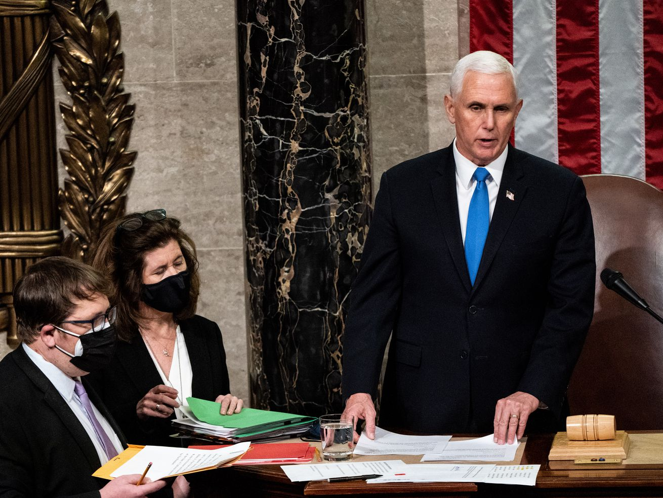Pence, in a dark suit, white shirt, and bright blue tie, stands in the House speaker's podium, front of a giant US flag. Aides hand him papers.