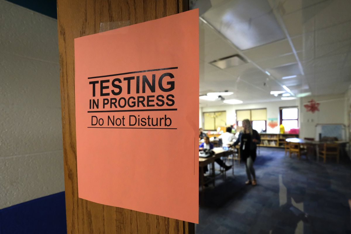 """An orange sign says """"testing in progress, do not disturb"""" as students work in the background"""