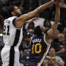 San Antonio Spurs forward Tim Duncan, left, defends Utah Jazz guard Alec Burks during the second half of an NBA basketball game, Wednesday, Jan. 15, 2014, in San Antonio. San Antonio won 109-105. (AP Photo/Darren Abate)