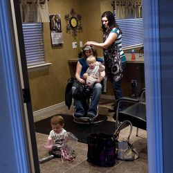 Jessica Bronson colors Karah Mackay's hair while Mackay's daughter sits on her lap and Bronson's son plays on the floor.