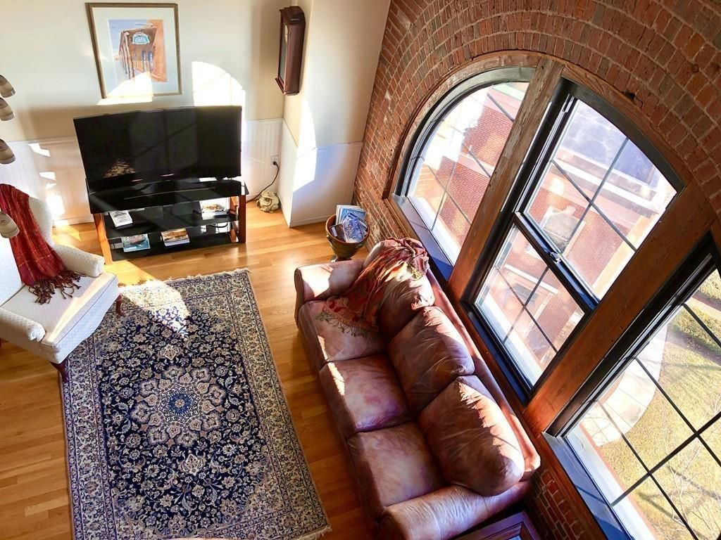 Ceiling view of a brick-walled living room with furniture and an enormous arched window.
