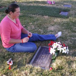 Sarah Robles sits at her father's grave in 2006, a short time after he died.