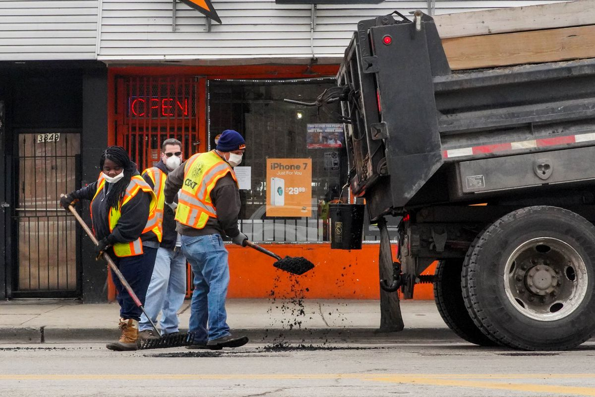Chicago Department of Transportation workers fill potholes Friday near Madison Street and Springfield Avenue as the Chicago Police Department's 11th District CAPS Office hosts Operation Clean.