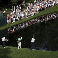 From left, Mark O'Meara, Tiger Woods and Sean O'Hair skip golf balls across the pond on the 16th hole during a practice round for the Masters golf tournament Wednesday, April 4, 2012, in Augusta, Ga.